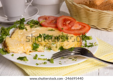 Scrambled eggs with cheese and fresh herbs on the table