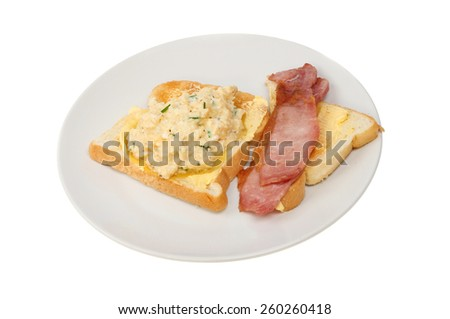 Scrambled eggs with chives and bacon on toast on a plate isolated against white - stock photo