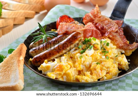 Scrambled eggs with fried bacon, fried sausages, grilled tomato and toast - stock photo