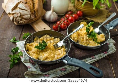 Scrambled eggs with herbs and homemade bread, on two frying pans - stock photo
