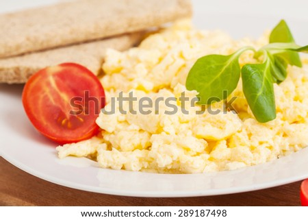 scrambled eggs with herbs and vegetables on the plate  - stock photo