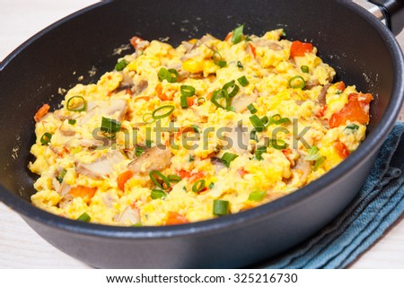 scrambled eggs with mushrooms and vegetables in a frying pan