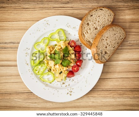 Scrambled eggs with paprika, cherry tomatoes, celery leaves and bread. Rich breakfast. - stock photo