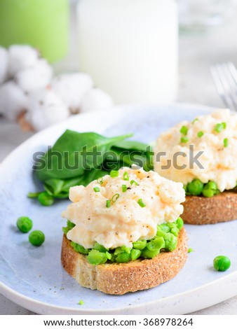 Scrambled eggs with peas on toasts