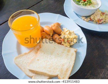Scrambled eggs with pork sausages, bread and orange juice on wood table, american breakfast