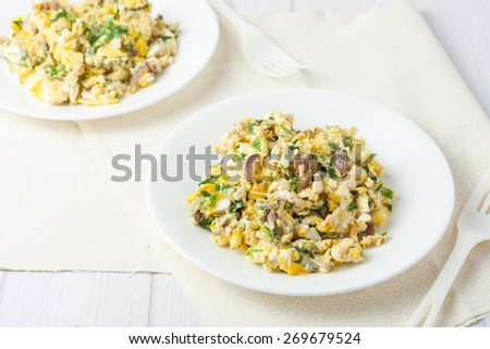 scrambled eggs with red onion and herbs on white plate