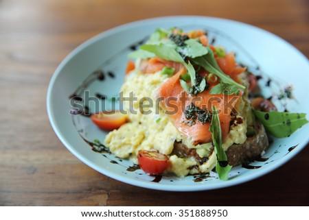 Scrambled eggs with smoked salmon and avocado - stock photo