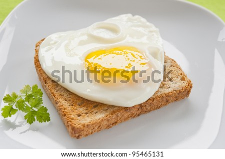 Scrambled eggs with toast on a white plate on a green cloth