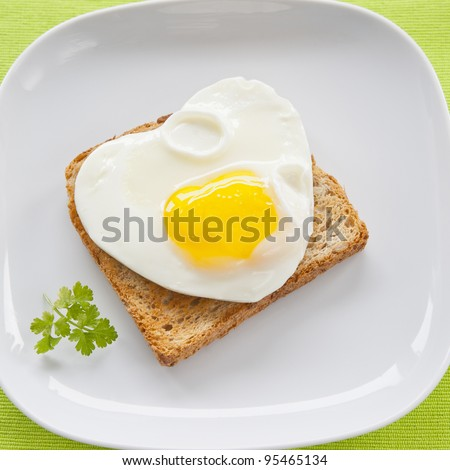 Scrambled eggs with toast on a white plate on a green cloth, framing square
