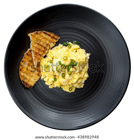 Scrambled eggs with toast on black plate. Top view, isolated on white.