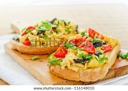 Scrambled eggs with tomato olives onion and parsley served on toast bread