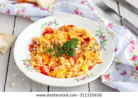 Scrambled Eggs With Tomatoes On A Plate With Bread