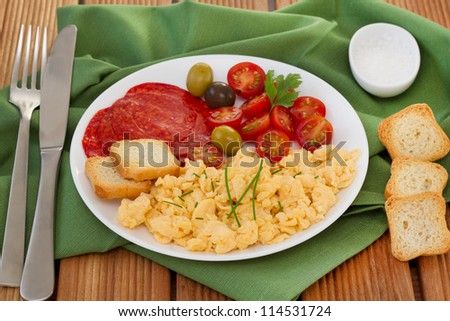 scrambles eggs with tomato and sausages on the plate