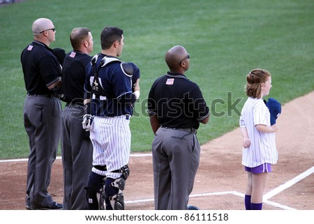 SCRANTON, PA - JULY 9: Umpires and players stand attentively during the National Anthema during the Rochester Red Wings/Scranton Wilkes Barre Yankees game, PNC Field on July 9, 2011 in Scranton, PA. - stock photo