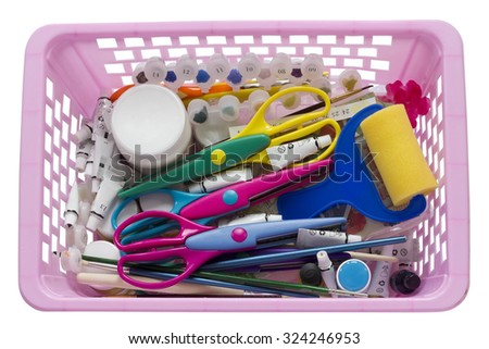 Scrap-booking tools in pink plastic basket - scissors, paper, brushes, tubes with paints and so on. Isolated
