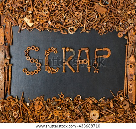 SCRAP made with rusty screws and bolts on black board with frame consisted of junk metal - stock photo