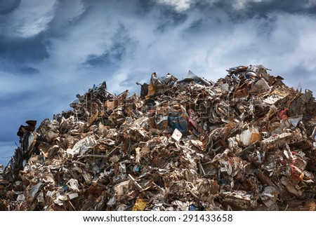 Scrap metal ready for recycling over dark clouds. - stock photo