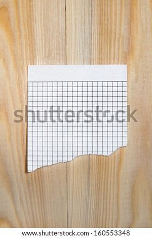 Scrap of paper sheet in a cage on a wooden surface  - stock photo
