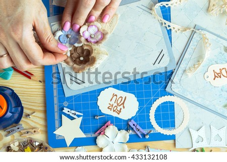 scrapbook background. Hands, Card and tools with decoration.