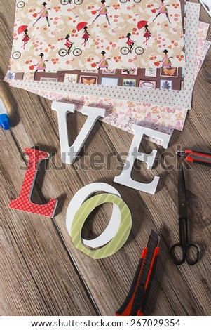 Scrapbook background with wooden LOVE letters and vintage paper, scissors, glue and cutter - stock photo