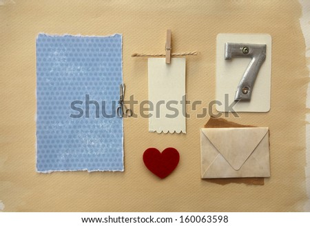 Scrapbook elements collection w metal seven number, empty tag label, envelope, love heart and blue paper scrap w small scissors detail. - stock photo