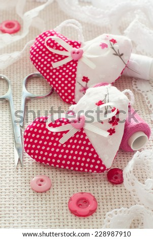 Scrapbook set for Valentines Day- hearts, spools of thread, buttons, laces over canvas background