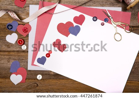 Scrapbooking background with craft paper, ribbon, buttons and heart cutouts. Space for your text. - stock photo