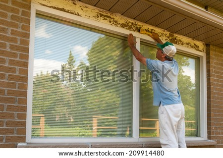 Scraping old paint from the window frame - stock photo