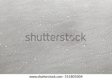 Scratched metal surface covered with water droplets