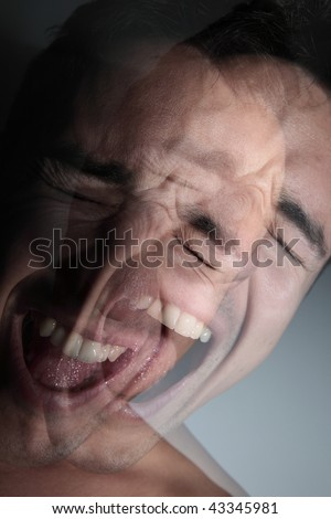 scream - young man's face deformed by a scream of anger/desperation/pain/rage (color toned image) - stock photo