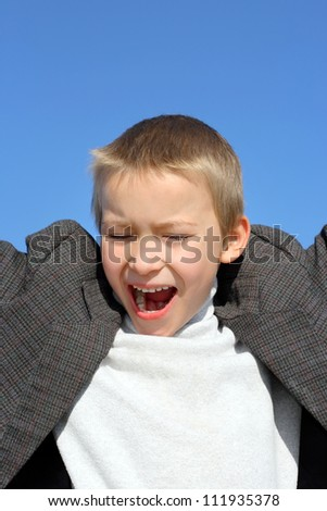 screaming boy on the blue sky background - stock photo