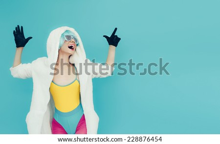 Screaming crazy Girl in hoodie on a blue background. Club dance style - stock photo
