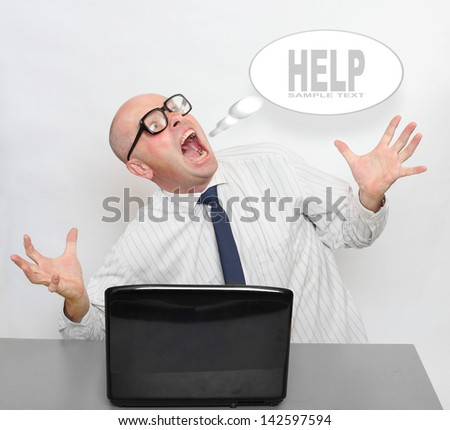 Screaming frustrated businessman with laptop on a desk in the office. Support concept. Picture with space for your text. - stock photo