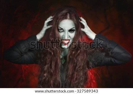 Screaming halloween beautiful vampire with long hair in hell