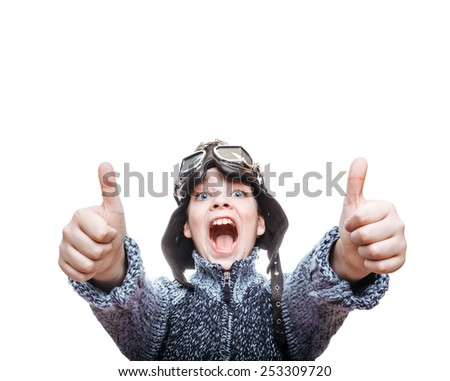 Screaming happy 10yrs boy in pilot helmet & goggles showing thumbs up. - stock photo