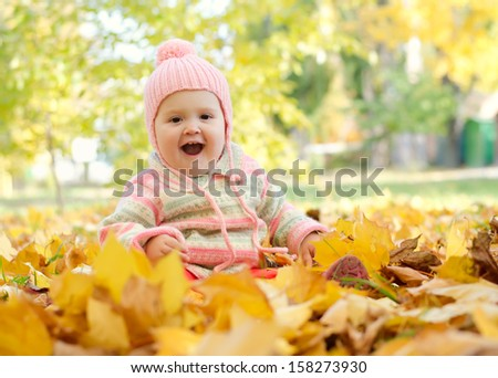 screaming little girl sitting in the autumn leaves in the park