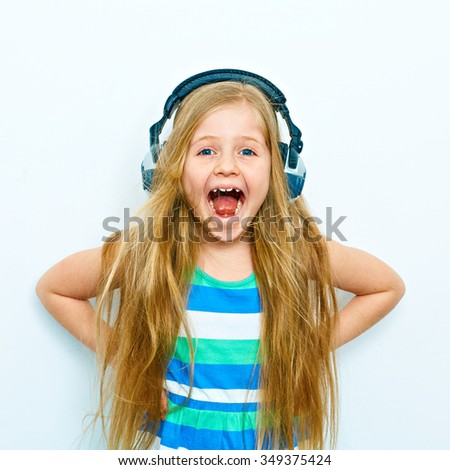 Screaming little girl with headphones funny portrait isolated on white background. - stock photo