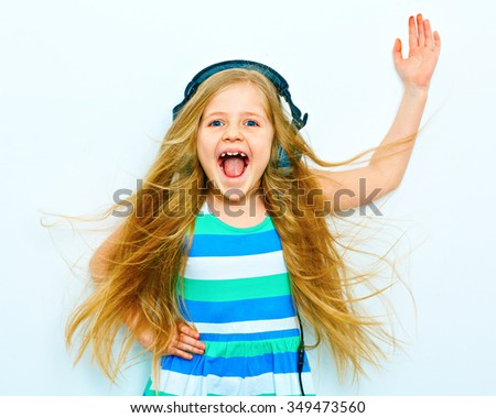 Screaming little girl with headphones funny portrait isolated on white background. One hand up. - stock photo