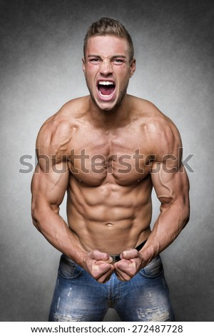 Screaming man with well trained body, biceps, abs and pecs and wearing a denim trousers - stock photo