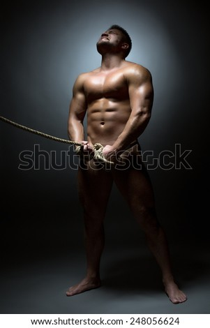 Screaming naked man bounded with rope - stock photo