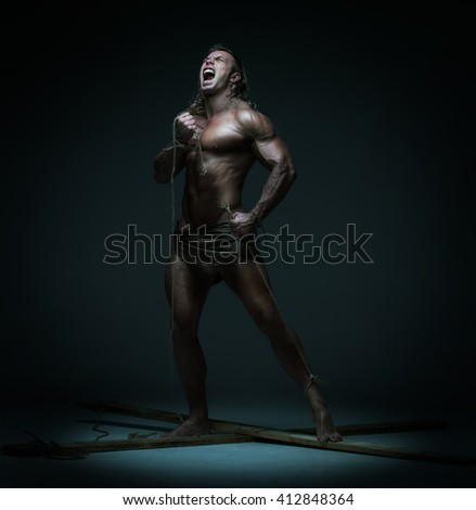 Screaming naked muscular man, hands tied rope to wooden beams