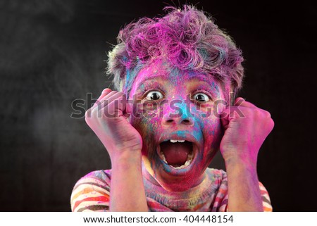 Screaming portrait of boy with face smeared with colored powder in a dark background. Concept for Indian festival Holi.  - stock photo