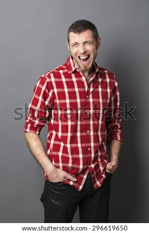 screaming 40's man wearing casual shirt shouting for anger and frustration with hands in jeans pockets