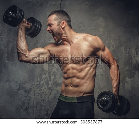 Screaming, shirtless muscular male working out with dumbbells on grey background.