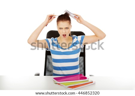 Screaming teen girl with book over her head - stock photo