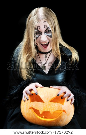 Screaming vampire girl with a halloween pumpkin on black background