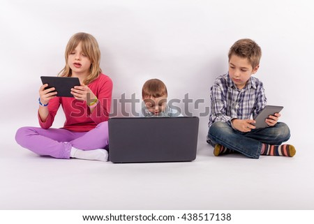 Screen addiction concept - sister and brother using tablets and their younger brother who is a baby using laptop - stock photo