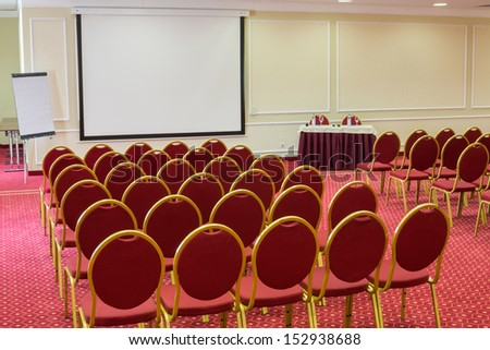Screen in empty conference hall with a red carpet on the floor - stock photo