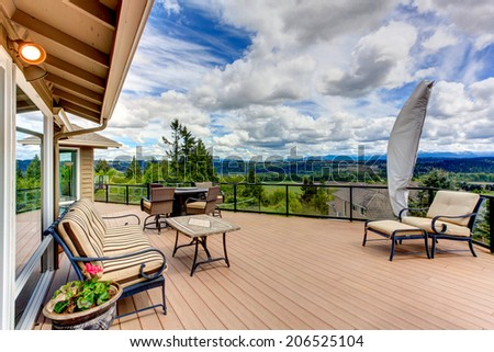 Screened walkout deck with fire pit, chairs, bench and coffee table - stock photo
