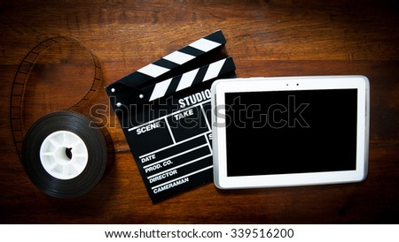 Screenwriter desktop with movie clapper board, film reel and notepad - stock photo